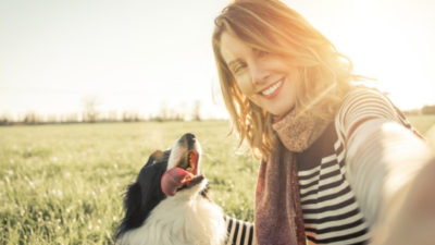 a woman and a dog at the field - BrokerCo will assist you in getting an insurance protection