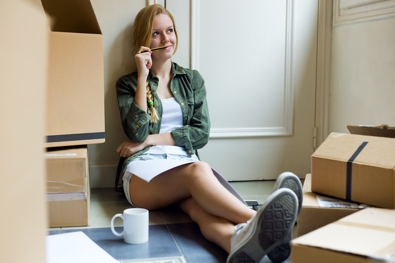 Portrait of young beautiful woman moving in new home.