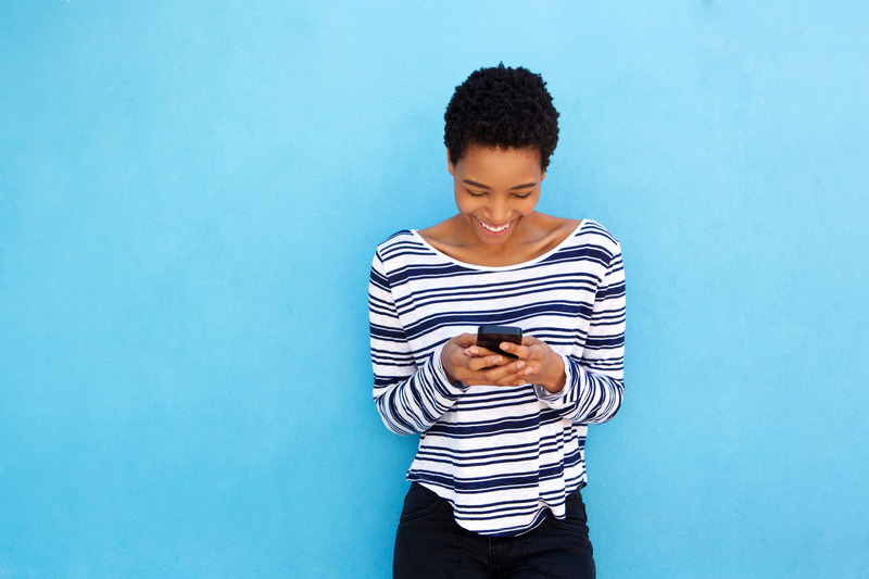 Portrait of happy black woman looking at mobile phone by blue background